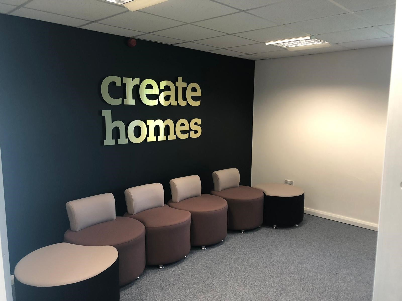 Create Homes Waiting Room with Create Homes gold signage placed above seating